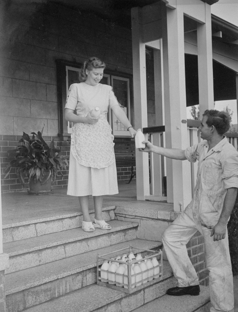 A milkman delivers milk to a woman at her home in 1950s Australia