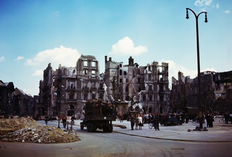 Berlin July, 1945. A Red Army truck can be seen carrying troops down a street lined with ruined buildings, rubble and crowds of civilians.