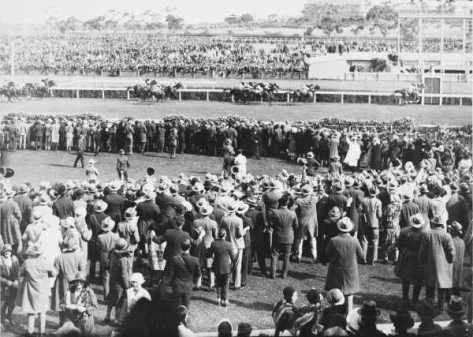 Phar Lap winning the Melbourne Cup Race from Second Wind and Shadow King on 5th November, 1930. Shows horses going over the finishing line viewed from over the heads of the crowd.