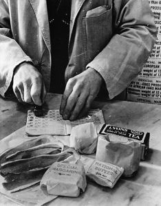 A shopkeeper cancels the coupons in a British housewife's ration book for the tea, sugar, cooking fats and bacon she is allowed for one week. April 1943.