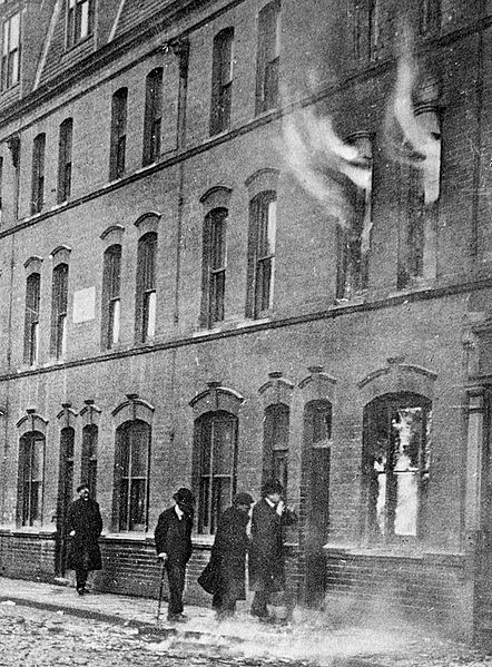 Detectives from Scotland Yard inspect the burning house at the centre of the Siege of Sidney Street, 3 January 1911. Note the debris on the street from the earlier gun battle.
