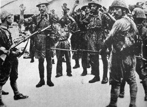 Surrendering troops of the Suffolk Regiment are held at gunpoint by Japanese infantry.