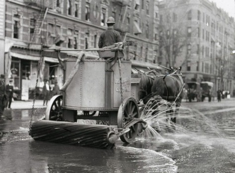 A two-horse team street cleaner, with sprayer, squeegee, and roller at rear. New York City.