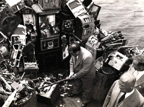 Aboard a police boat on October 10, 1934, New York Mayor Fiorello LaGuardia hacks away at confiscated slot machines about to be destroyed and dumped into New York harbor.