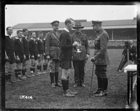 King_George_V_presents_a_cup_to_the_captain_of_the_winning_New_Zealand_Services_Rugby_Team,_LondonKing George V presents a cup to the captain of the winning New Zealand Services Rugby Team, London. 16 April 1919.