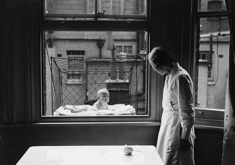 A nanny is pictured supervising a baby suspended in a wire cage attached to the outside of a flat window in Chelsea, London in 1937.