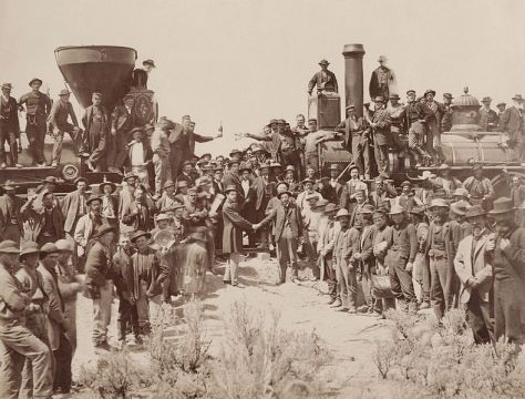 East_and_West_Shaking_hands_at_the_laying_of_last_rail_Union_Pacific_Railroad_-_RestorationA.J. Russell image of the celebration following the driving of the Last Spike at Promontory Summit, U.T., May 10, 1869.