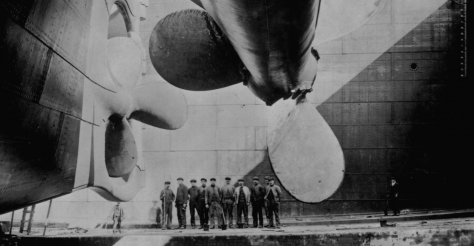 Shipbuilders gather underneath one of the Titanic's propellers (1912).
