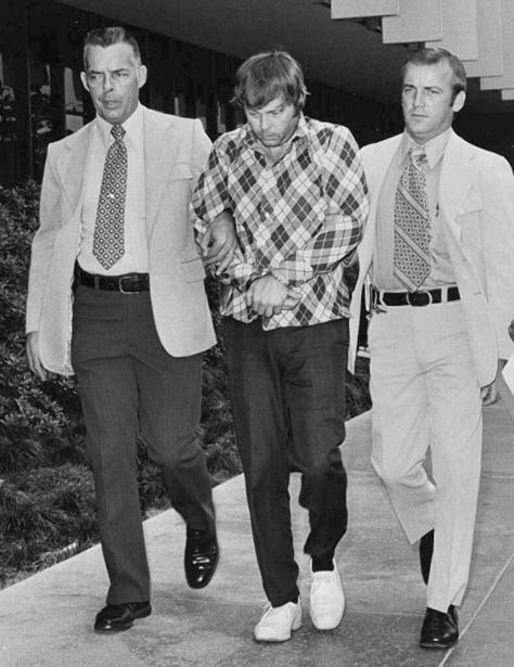 Edward C. Allaway (c.), alleged killer of seven people at California State University two days earlier, is led into Orange County courthouse July 14,1976.