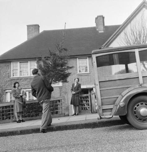 a-representative-of-the-ymca-delivers-a-christmas-tree-to-mrs-devereux-in-pinner-the-tree-is-a-present-from-her-husband-serving-in-the-arm-and-purchased-through-the-gifts-to-home-league-of-the-ymc