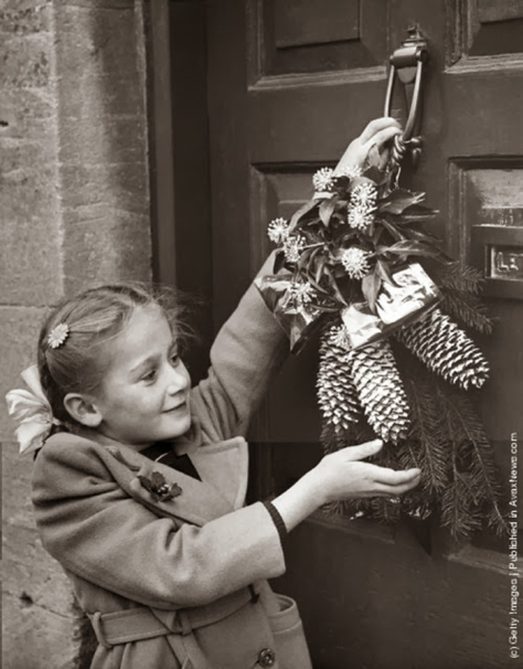 old-christmas-photos-10december-24-1954-a-young-girl-hangs-a-christmas-garland-on-the-door-of-her-home-at-northleach-gloucestershire-in-accordance-with-an-old-local-tradition