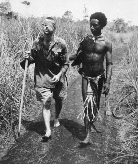 buna-papua-25-december-1942-qx23902-private-george-c-dick-whittington-being-helped-towards-a-field-hospital-at-dobodura-papuan-native-is-fuzzy-wuzzy-angel-raphael-oimbari