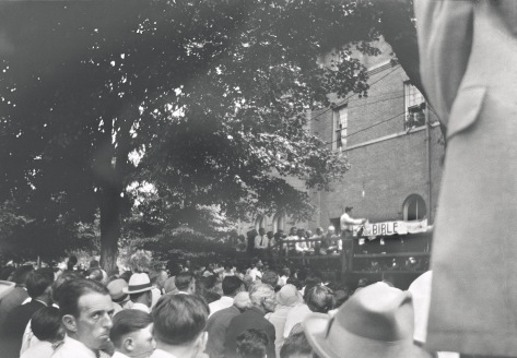 """Tennessee verses John T. Scopes Trial, """"Dayton, Tennessee"""", July 1925,  William Silverman Photographs, accession #10-042, View of trial proceedings outdoors (man taking down """"Read Your Bible"""" sign)"""