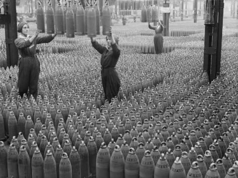 Female munitions workers guide 6 inch howitzer shells being lowered to the floor at the Chilwell ammunition factory in Nottinghamshire, UK. July 1917.