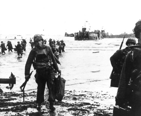 Normandy_1 Carrying their equipment, U.S. assault troops move onto Utah Beach. Landing craft can be seen in the background. 6th June 1944 D-Day Normandy landings.