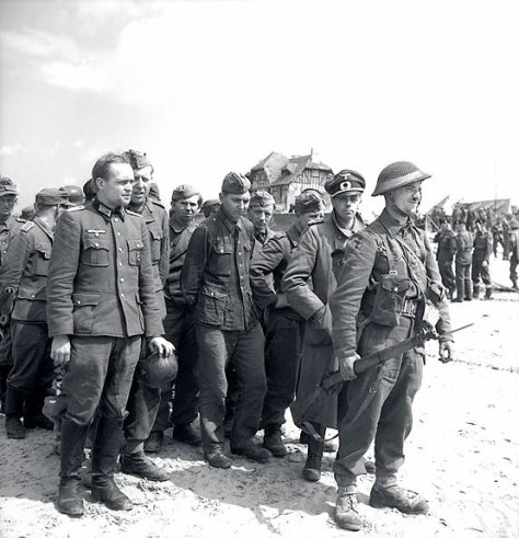 Group_of_prisoners_who_surrendered_to_Canadians_in_Courseulles Two German officers in a group of prisoners who surrendered to Canadian troops in Courseulles-sur-Mer - June 6, 1944. Secon