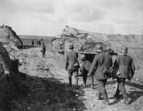 Battle of the Canal du Nord. German prisoners, carrying a wounded man, follow a British tank through a cutting made in the bank of the Canal du Nord near Moeuvres, 27th September 1918. F