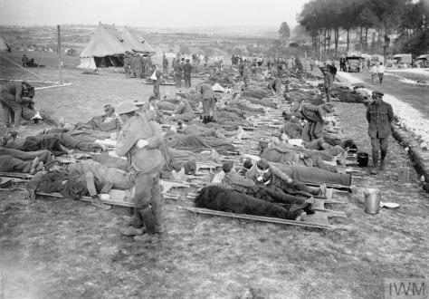 Wounded soldiers await transport to hospital near Albert, Somme on the 12th of September, 1916 in this photograph by Ernest Brooks. First World War.