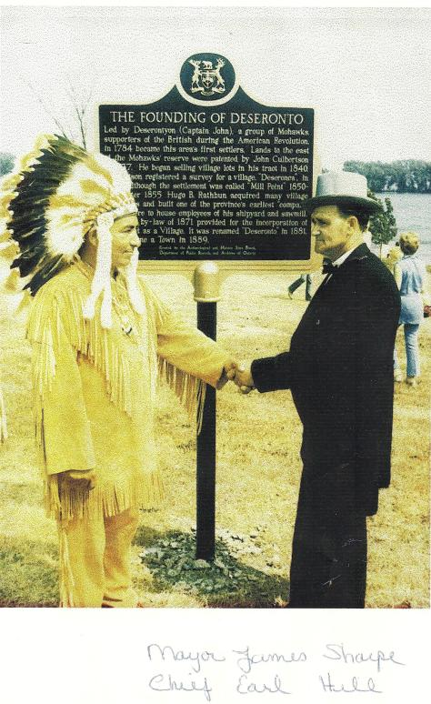 Copy of a photograph of Mayor James Sharpe and Chief Earl Hill, taken in front of the memorial plaque in Centennial Park, Deseronto, Ontario, on the occasion of the celebration of the to