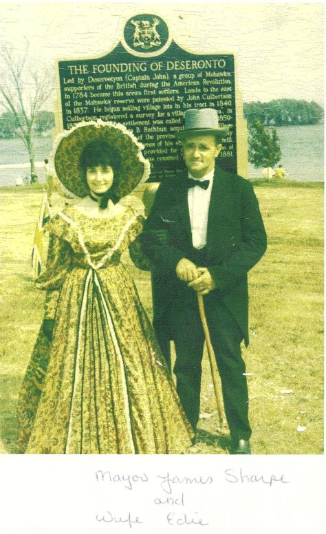Copy of a photograph of Mayor James Sharpe and his wife, Edie, taken in front of the memorial plaque in Centennial Park, Deseronto, Ontario, on the occasion of the celebration of the tow