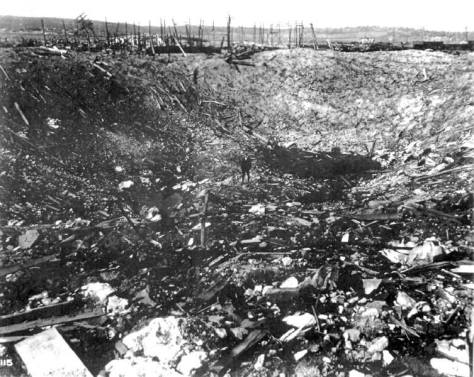 GillespieExplosion Man standing in a large crater from T. A. Gillespie Company Shell Loading Plant explosion in Sayreville, New Jersey. October 1918. World War One.