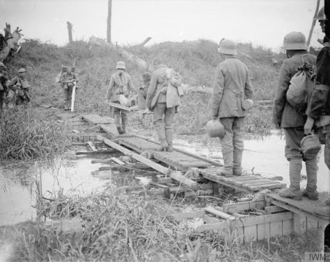 The_Battle_of_Passchendaele,_July-november_1917_Battle of Pilckem Ridge. German prisoners and British wounded crossing a duck board bridge over the Yser Canal. Near Boesinghe, 31 July 19
