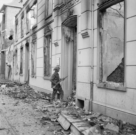 A soldier of 6th King's Own Scottish Borderers, 15th (Scottish) Division, searches wrecked buildings in Blerick, a suburb of Venlo in Holland, 5 December 1944. second World war Two Black