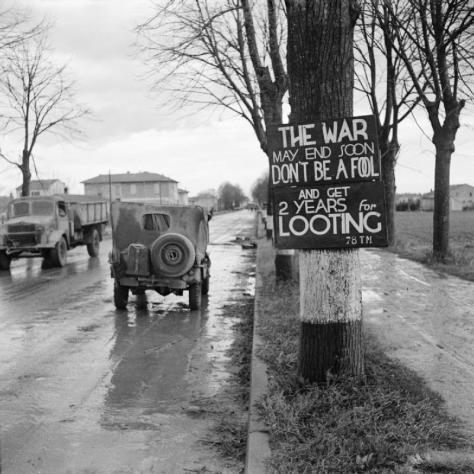 Second World War Two Black and White Vintage 1940s A British jeep passes a sign warning against looting on the outskirts of Ravenna, Italy, 7 December 1944.