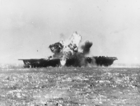 The U.S. Navy aircraft carrier USS Essex (CV-9) is hit on the flight deck amidships by a Japanese Kamikaze, during operations off the Philippines, 25 November 1944.