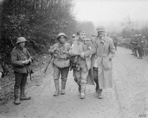 The_Battle_of_the_Somme,_July-november_1916_Battle of the Ancre. An Army Chaplain of the Army Chaplains' Department helping along a wounded German prisoner taken on the 13th of November