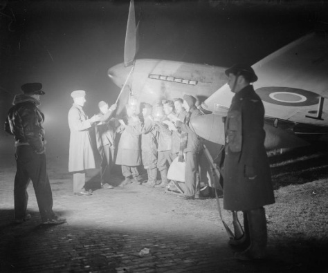 1944 Members of a British Royal Air Force ground crew sing Christmas carols for an officer and guard while stationed at Volkel Air Base in the Netherlands during the Second World War
