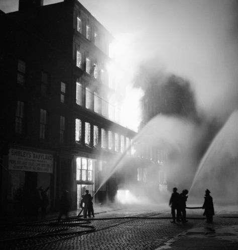Buildings burning in Manchester after a German air raid on the night of 23 December 1940. Second World War Two Black and White Vintage