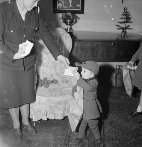 Bwrs Christmas Gifts Distributed To London's East Enders- American Aid To the Canning Town Settlement, London, England, UK, December 1944.Derek Cunningham receives a Christmas card and s