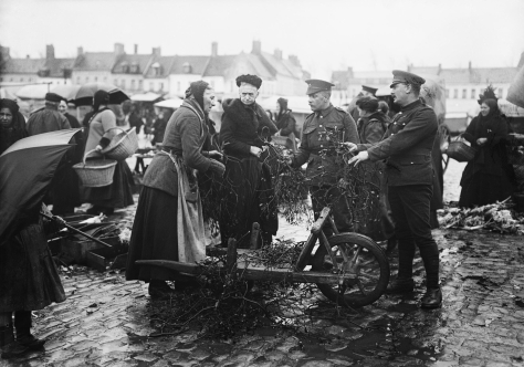 Christmas_on_the_Western_Front,_1914-1918_Q1628British troops (the soldier on the left thought to be of the Worcestershire Regiment) purchasing mistletoe from women on a market, Bailleul