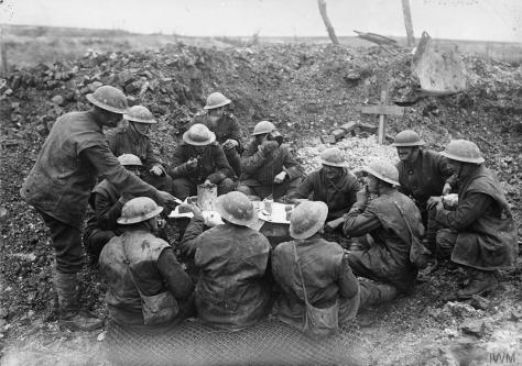 Christmas_on_the_Western_Front,_1914-1918_Q1630British troops eating their Christmas dinner in a shell hole, Beaumont Hamel, 25th December 1916. First World War One