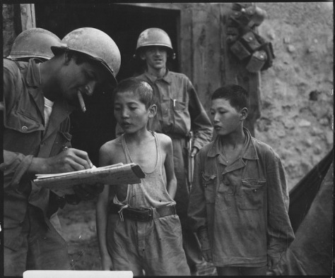 18th September 1950 Two North Korean boys, serving in the North Korean Army, taken prisoner in the Sindang-dong area by elements of the 389th Infantry Regiment, are interrogated by a U.S