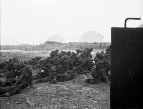 Infantry_waiting_to_move_off_'Queen_White'_BeachBritish troops take cover after landing on Sword Beach. D-Day Normandy landings. 6th june 1944.