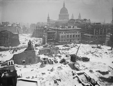 bombed-london-in-the-snowThe destruction around St Paul's Cathedral air raid on London is softened by a heavy dusting of snow. mobile crane and truck can be seen work to clear up some of