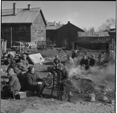 Soviet women having breakfast next to a burning pile of rubbish at a Finnish concentration camp in Petrozavodsk, Karelia, during the Continuation War. 24th April 1942. Second World War T