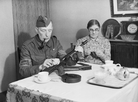 A veteran sergeant in the Dorking Home Guard cleans his Tommy gun at the dining room table, before going on parade, 1 December 1940. Second World War Two