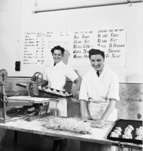 Two WAAF cooks at an Royal Air Force aerodrome, following recipes for a hundred pies and a hundred scones. September 1940.