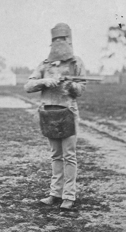 PolicemanWearingKellyArmourPhotograph taken on 5 July 1880 of a policeman equipped with Byrne's helmet and Ned Kelly's rifle and skull cap. Bushranger.