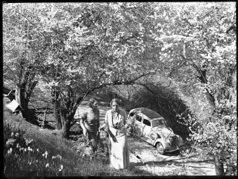 Two women walking up a hill, a 1930s Vauxhall car 211- 651, spring blossoms, possibly in the Cotter Reserve near Canberra, 1938-1950s) (Australian Capital Territory) - (Frank Hurley) (9714560980)