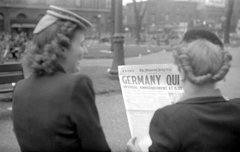 7th May 1945 Two women stand on Saint Catherine Street reading the front page of The Montreal Daily Star. The newspaper announces Germany Quit - signalling the end of the Second World War in Europe.